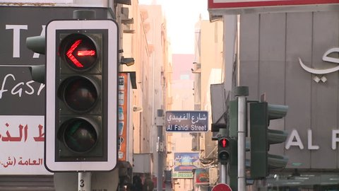 DUBAI, UAE - CIRCA 2009: Tilt down from the Al Fahidi Street sign, in Bur Dubai, to the busy pedestrian street, showing shop signs, traffic signals and pedestrians.