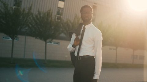 Attractive confident african american businessman walking near office center holding jacket over his shoulder. Man going home after work. Sun rays. Close up