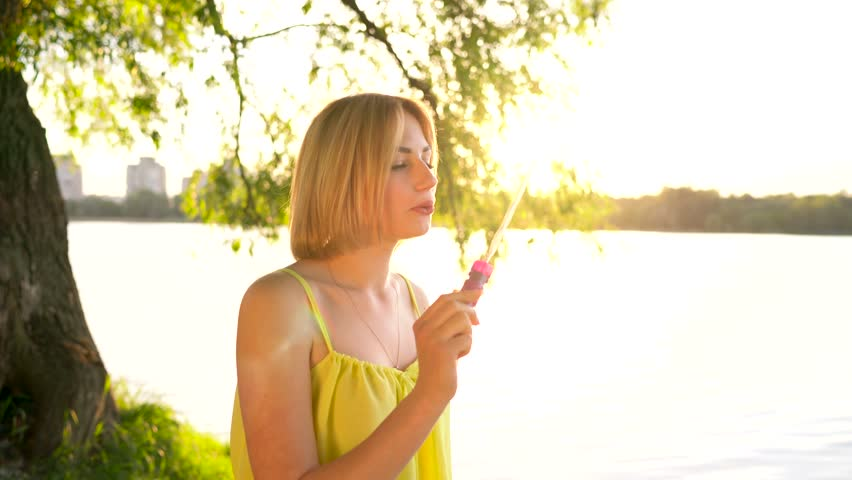 Young beautiful blonde blowing soap bubbles outdoors