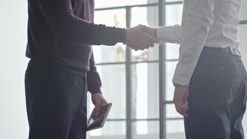 Tilt up of bearded businessman in casual clothing holding tablet and shaking hands with male colleague before panoramic window, then discussing work | Shutterstock HD Video #27462052