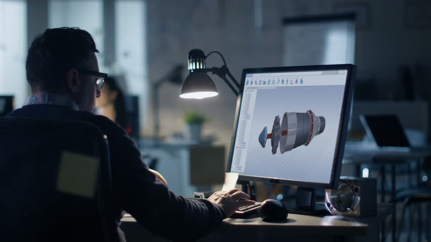 Late at Night in the Office. Design Engineer Works on His Personal Computer. On His Display We See Blueprints. Office Looks Modern. In the Background People Working.  | Shutterstock HD Video #27466381