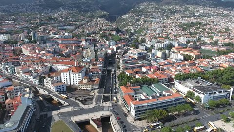 Aerial view of centre of historic city of Funchal in Madeira, with backdrop of houses on the hills, waterfront promenade, beach .