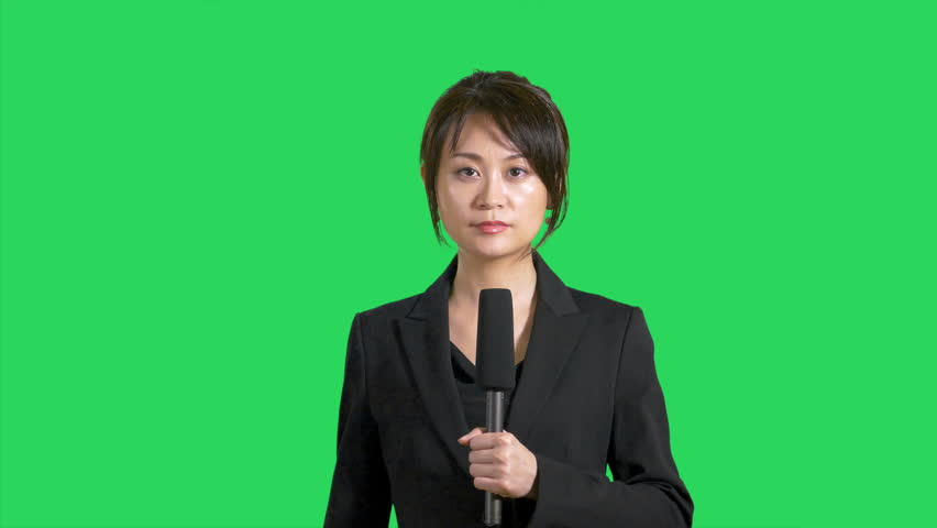 Serious Asian news reporter on green screen
