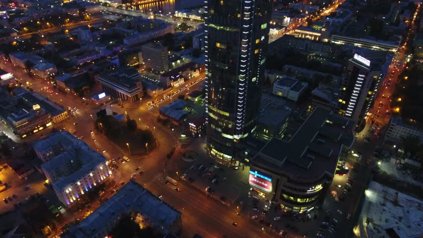 Unique flyover Yekaterinburg City Vysotsky tallest business skyscraper Russia. Colorful evening night illumination. Eltsyn center at background skyline. Aerial drone flight above forward. Fifa 2018
