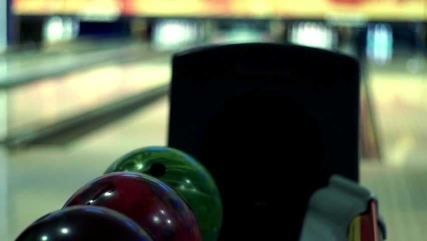 Bowling game. Bowling balls lie on stand close up. Player holds bowling ball with hand
