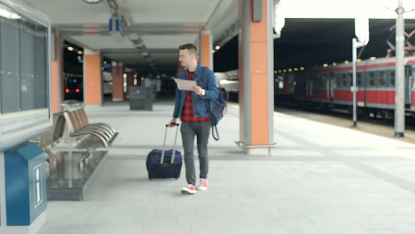 Stylish man walking with a suitcase and reading map on the train station, steadycam shot  | Shutterstock HD Video #27519541