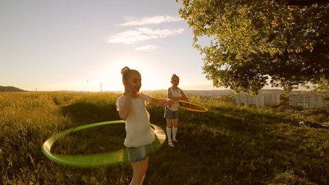 Two kids girls play with hula-hoop outside on sunset / Two kids girls play with hula-hoop
