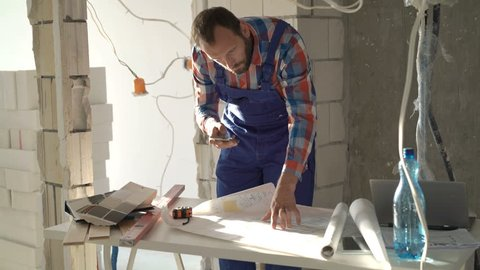 Male worker working with smartphone and blueprints during renovation at new home