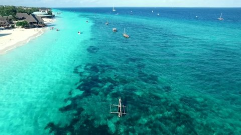 Beautiful overview of coastal line with boats sitting on water, sunny day, Zanzibar, Tanzania, aerial
