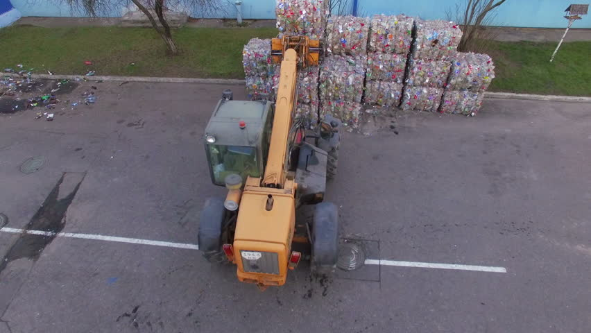 The loader loads the trailer with bales of compressed plastic. Aerial view. Drone view. Drone footage. 4K. Processing of plastics. Renewable energy sources.