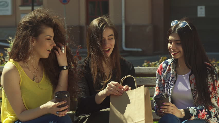 Pretty caucasian girl bragging about shopping to her friends. Three young women sitting on the bench outdoors. Attractive female teenagers looking inside the bag | Shutterstock HD Video #27653461