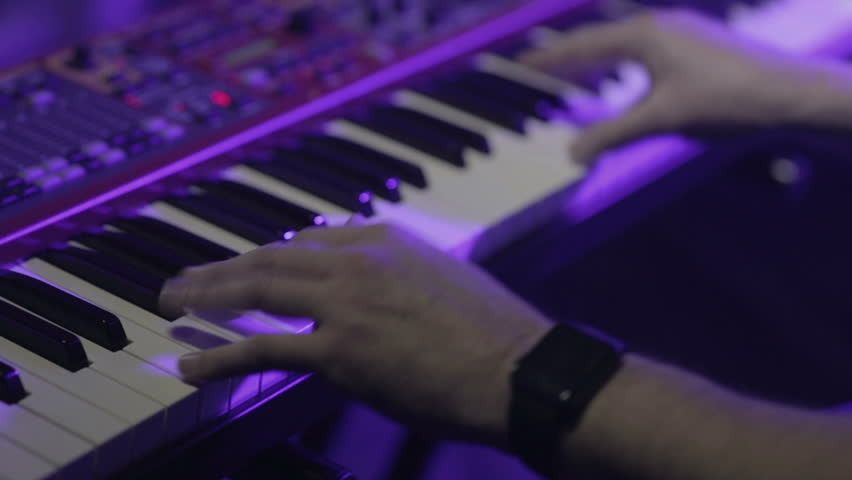 Musician playing on the keyboard synthesizer piano keys. Musician plays a musical instrument on the concert stage
