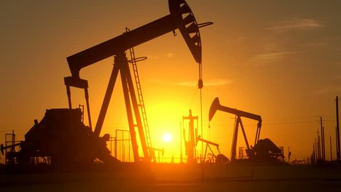 The silhouette of oil pumps in a large oil field at sunrise.