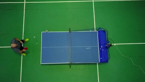 Top view of table tennis player returning balls from the ball machine