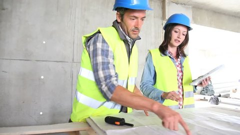 Architect and foreman checking construction project on tablet