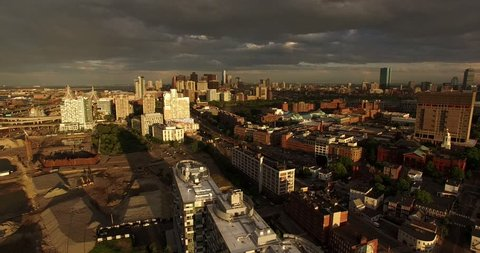 Aerial shot looking over construction site and gorgeous Boston skyline lit by setting sun
