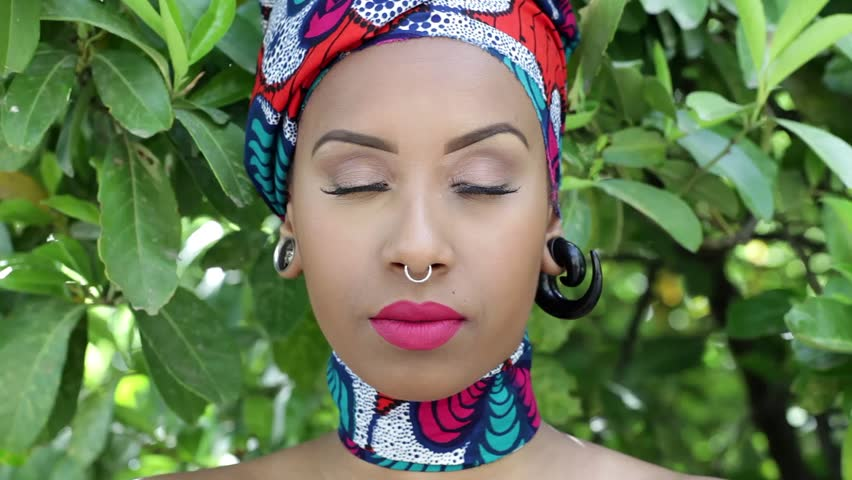 Eyes opening of young woman with piercings wearing traditional Brazilian headgear