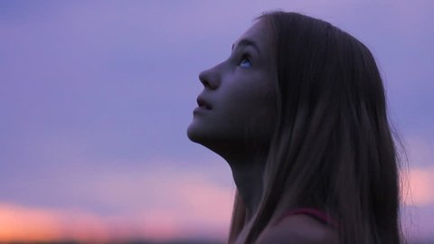 Beautiful girl praying looking up at purple sky with hope, close-up. Silhouette of young woman dreaming looking upwards sunset outdoors.