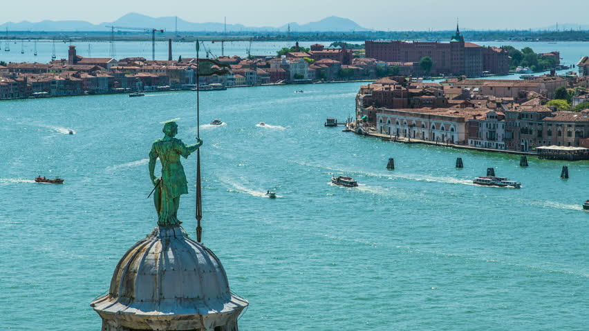 Top of belfry with Saint George statue in Venice, traffic on Grand Canal, travel