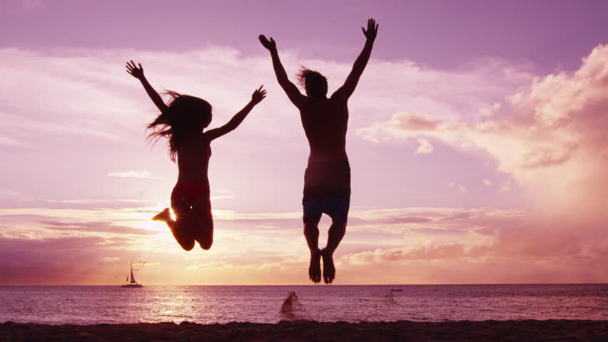 Happy couple jumping on beach enjoying sunset on summer travel vacation holiday. Happiness and bliss concept video with people jumping of joy celebrating in silhouette. SLOW MOTION RED EPIC. | Shutterstock HD Video #27730501