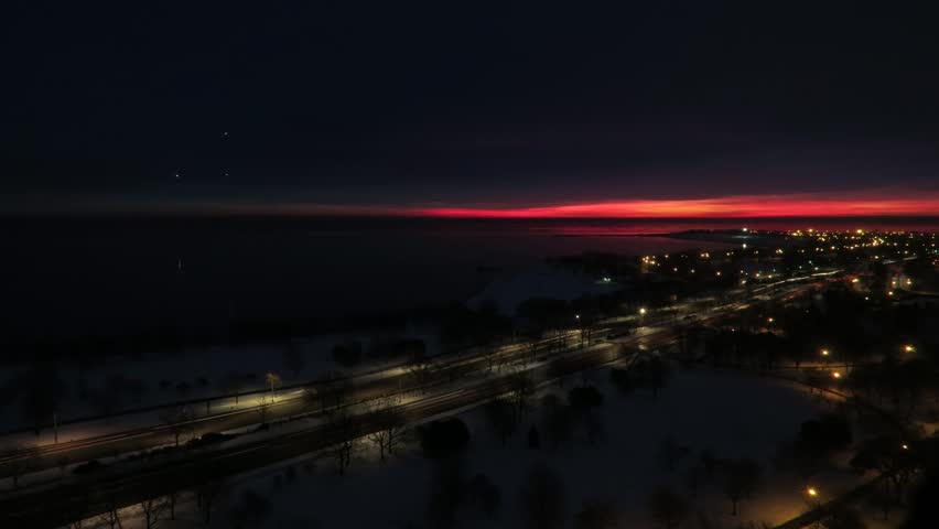 Dramatic vivid winter sunrise timelapse view over Lake Michigan shoreline in Chicago in rich pink purple and blue colors with planes flying overhead and snow and cars in the foreground