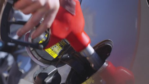 Closeup slow motion shot of male hand taking off fuel cap and inserting nozzle into car tank at gas station; woman drinking coffee in background
