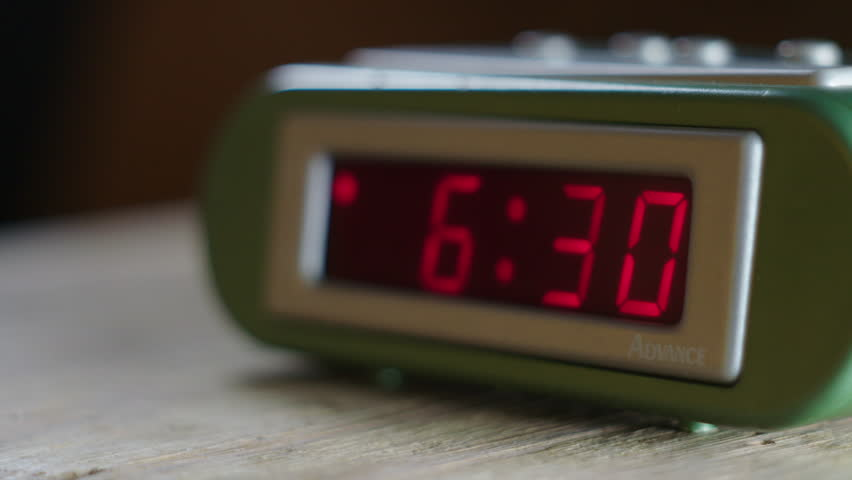 Morning alarm clock -- time changes from 6:29 to 6:30 as camera pans across