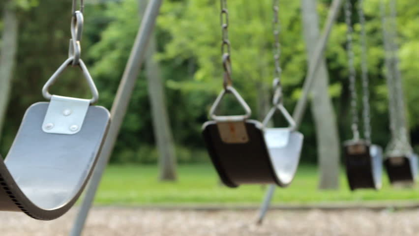 Empty swings swaying at playground