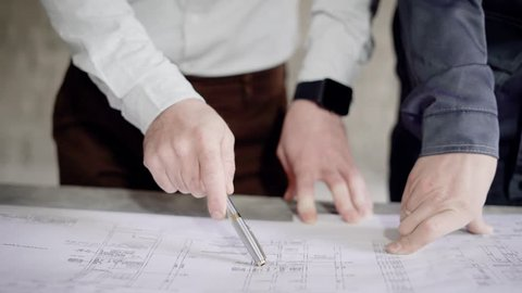 Businessman at the construction site. There is a discussion of the main drawing and the plan of construction between the founder and the master master.