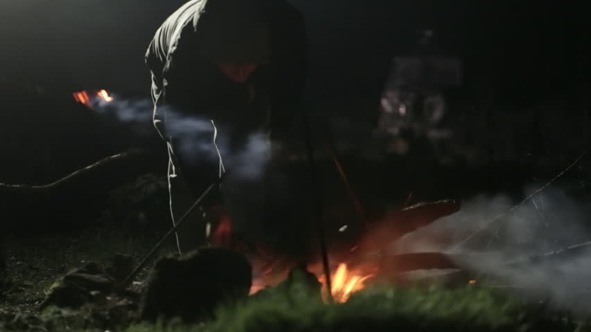 Campfire at night. Man adding the woods in bonfire and correcting coals. Smoke and wind in dim light. | Shutterstock HD Video #27789181