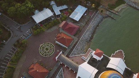 Aerial Footage - Dawn at a mosque, The Melaka Straits Mosque, located on the man-made Malacca Island near Melaka City, Melaka, Malaysia. Color corrected with film look color LUT. Moody exposure.