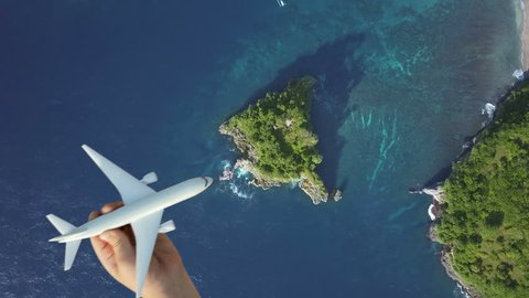 Travel around the world by air transport, summer vacation concept on nature landscape, blue lagoon background. Scenic aerial view of child hand playing plane, flying above azure water of ocean, island