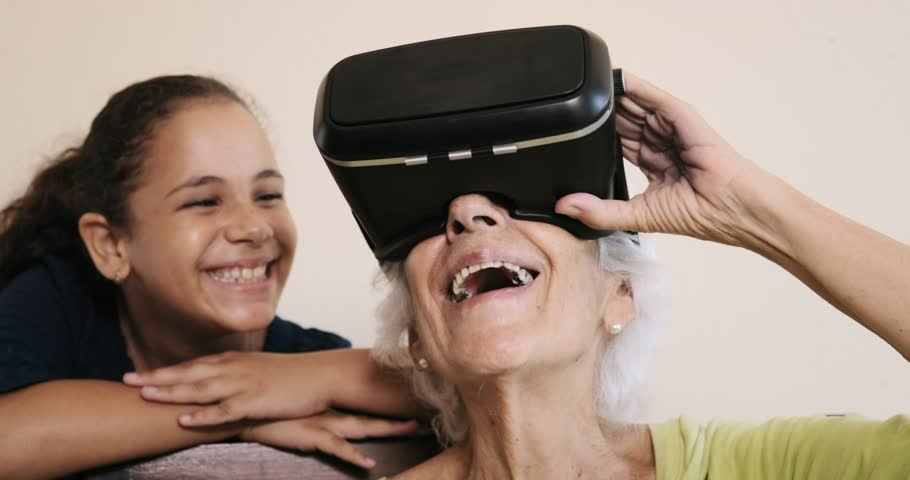 Family relationship between grandmother and granddaughter. Grandma and female grandchild. Happy old woman playing virtual reality with little girl at home. VR, 3D video and technology. Slow motion