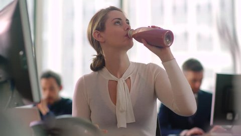 Woman sips a healthy smoothie drink whilst working at her desk.