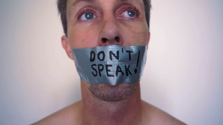 Close up head shot of a guy with his mouth covered with duct tape and the words don't speak written on it.