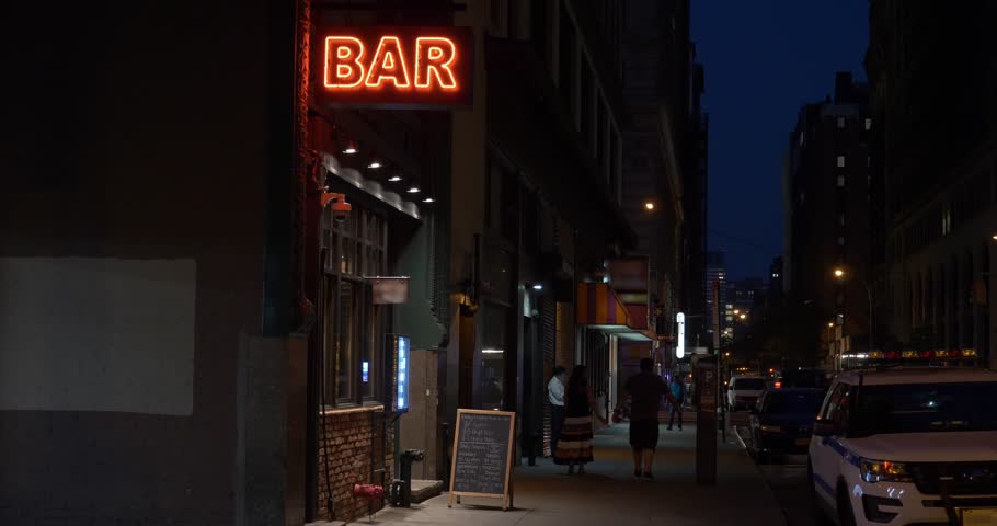 A nighttime exterior establishing shot of a generic, unbranded bar and restaurant in downtown Manhattan, New York City. Day/Night matching available.