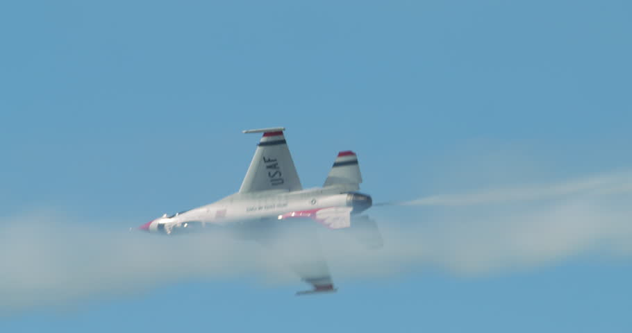 TITUSVILLE, FLORIDA - CIRCA MARCH 2017: USAF Thunderbirds Demonstration Team performs at airshow - single F18 jet passes with smoke trail in slow motion