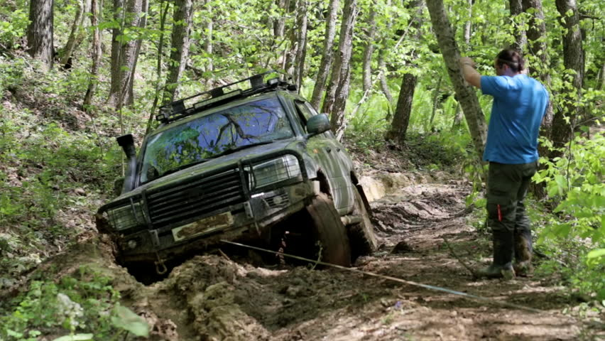 Expeditionary SUV got stuck in the forest and trying to get out via winch. Man next to vehicle helps driver overcome an obstacle. | Shutterstock HD Video #27867751