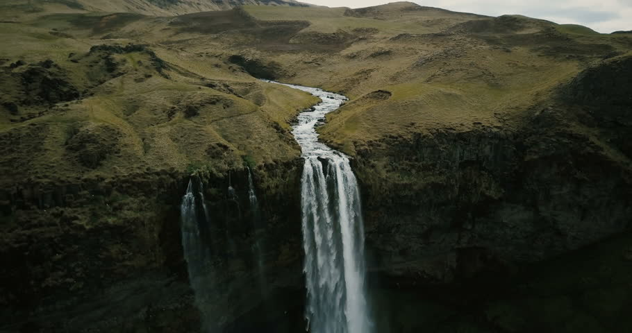 Aerial view to the mountains river flows through the valley and falls down. Waterfall Seljalandsfoss in Iceland.