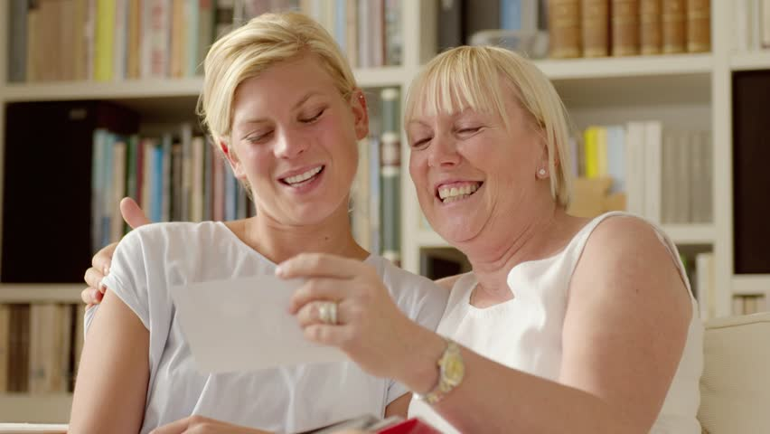 Family happiness and memories, happy mother and daughter looking at pictures in photo album at home