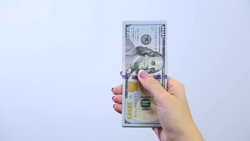 Closeup of 2 adult female caucasian hands holding many banknotes of us dollars isolated on white background. Woman counting 100 $ bills. Real time full hd video footage.