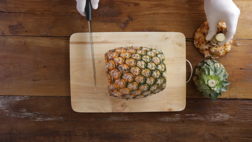 Cutting pineapple, Chef hands with white latex gloves to cutting pineapple on wooden board, Close-up, Top view.