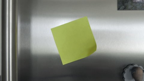 Yellow post it note on a fridge. The note is in an angle. Tracking in shot.
