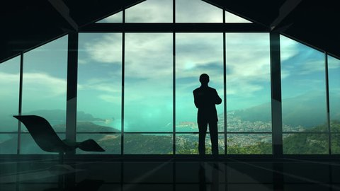 A man is standing by the window viewing IOT infographics elements