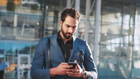 Attractive bearded businessman looking around and using his smartphone while coming out of the modern glassy building, airport or office in a bright light. Stylish look, playful mood.