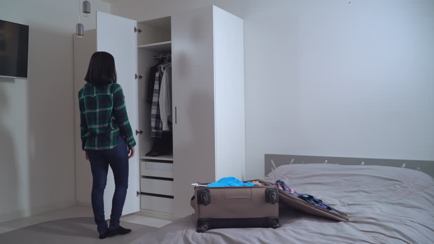 Lady try on dress and put it in suitcase. Young woman wearing in casual clothes packing bag planning vocation. Caucasian girl with black hair in apartment. #27929794