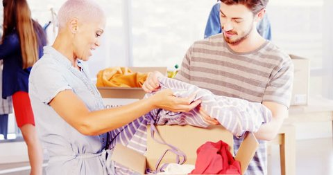 Happy creative executive team sorting clothes in donation box in office