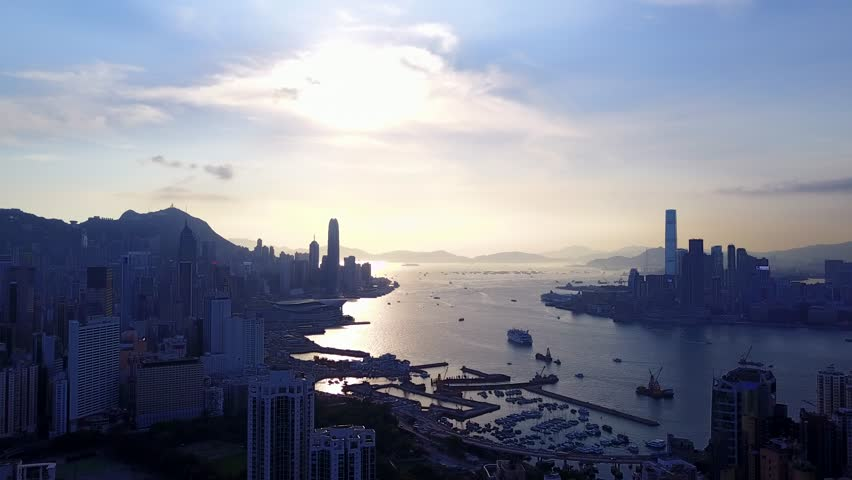 Famous Victoria Harbour and Hong Kong downtown dark cityscape from height, evening shot. Crowded urban area on both sides of channel, silhouettes of buildings, mountains and small boats and ships | Shutterstock HD Video #27943711