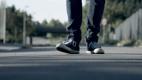 Young man's sneakers tapping on asphalt road.