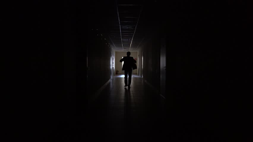 Woman In Black Dress Walking Down Dark Hallway Stock
